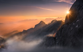 Picture the sun, light, mountains, fog, rocks, people