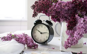 Picture table, watch, pencils, alarm clock, vase, notebook, lilac, bokeh