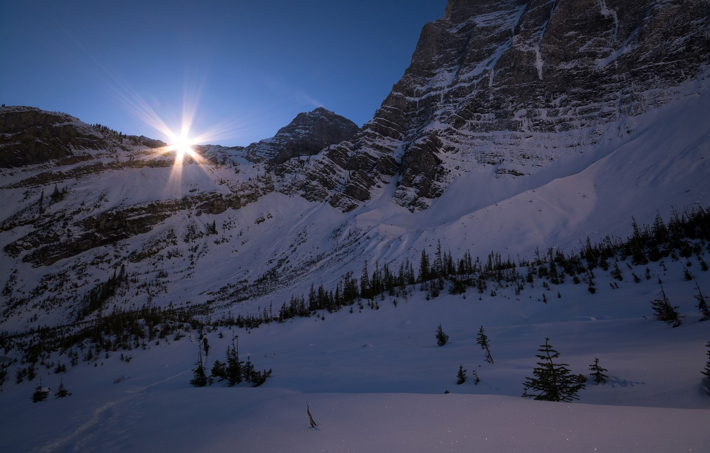 Photo wallpaper winter, the sky, the sun, rays, snow, trees, mountains, stones, rocks, slope, Canada, Albert, Banff …