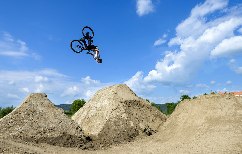 Photo wallpaper the sky, the sun, clouds, bike, helmet, guy, jump, flip, the trick
