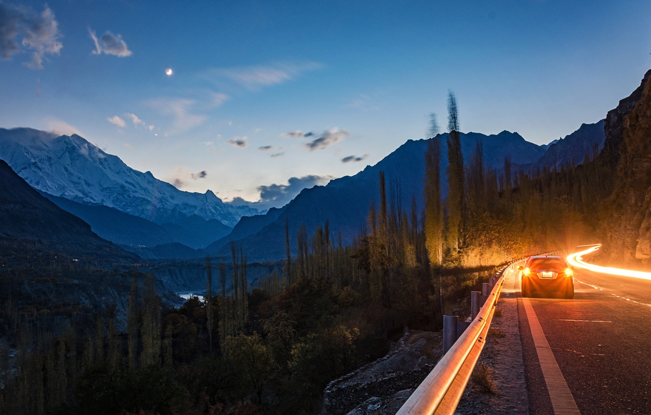 Photo wallpaper road, forest, trees, mountains, lights, rocks, the evening, canyon, river, car, headlights, Pakistan, Hunza