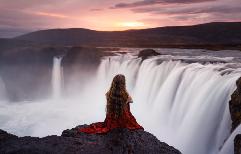 Photo wallpaper girl, sunset, mountains, mood, rocks, waterfall, sitting, red dress, long-haired