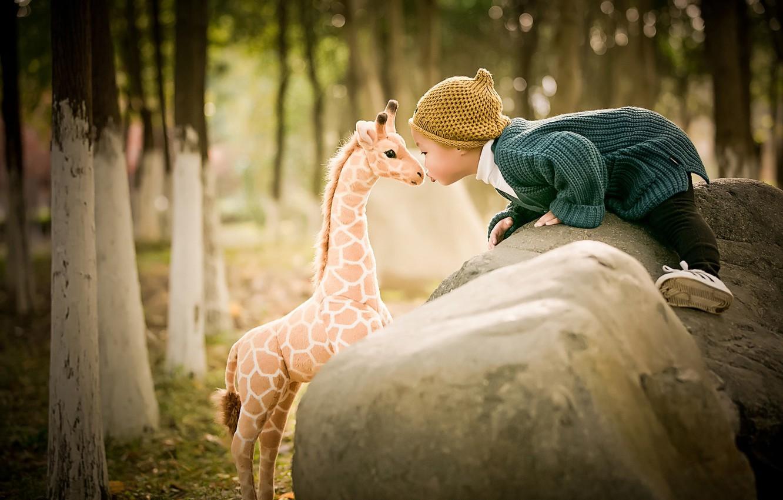 Photo wallpaper trees, nature, stones, toy, kiss, baby, giraffe, jacket, child, cap, boulders
