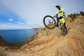 Picture sea, mountains, bike, rocks, coast, costume, gloves, helmet, athlete, extreme